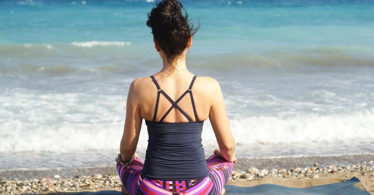 Girl sitting on a sunny beach doing yoga and getting vitamin d from the sun